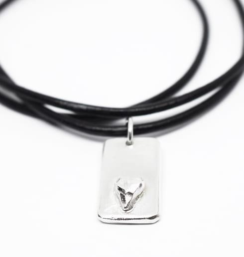silverbricka med hjärta i läderrem på vit botten
