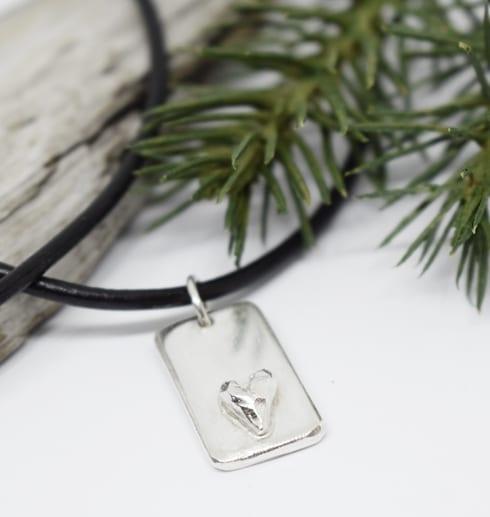 silverbricka med hjärta i läderrem på vit botten med träbit och grankvist
