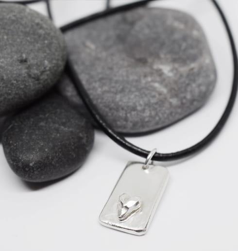 silverbricka med hjärta som hänger i en läderrem på vit botten med grå stenar