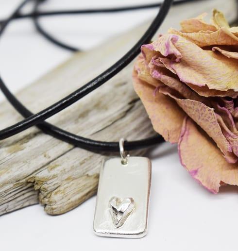 Silverbricka med hjärta som hänger i en läderrem på träbot med ros bredvid