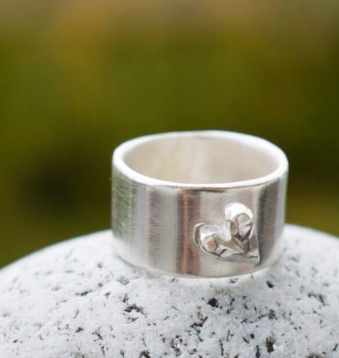 silverring med hjärta på sten utomhus