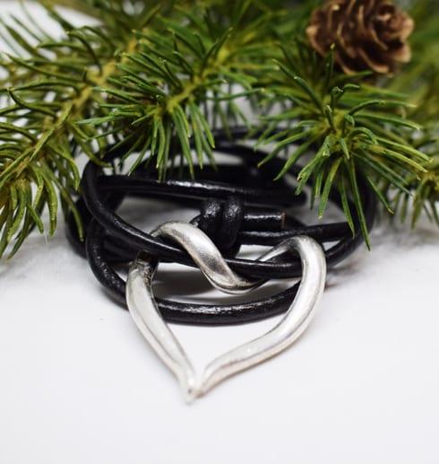silverhjärta i läderrem med grankvist bakom