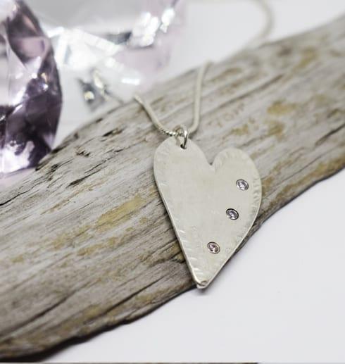 silverhjärta med stenar på träbit med diamant bakom