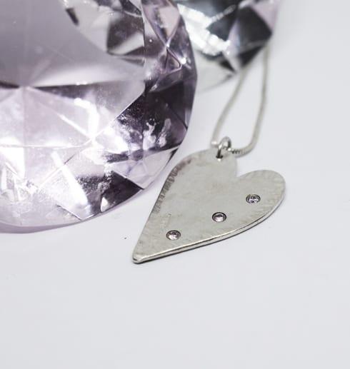 silverhjärta med stenar på vit botten med diamant bakom