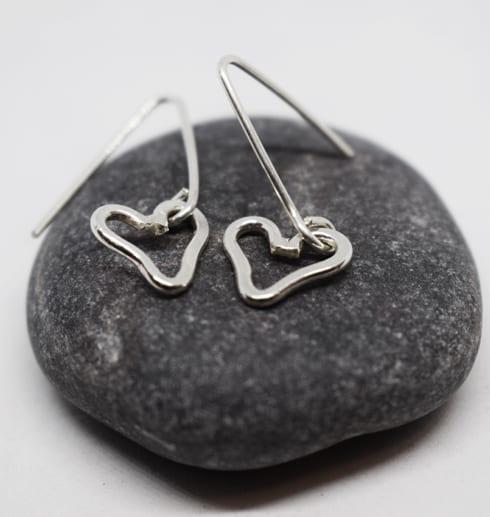 hjärtörhängen i silver på grå sten