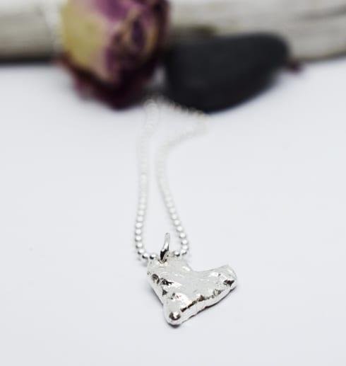 silverhjärta på vit bakgrund med rosor bakom