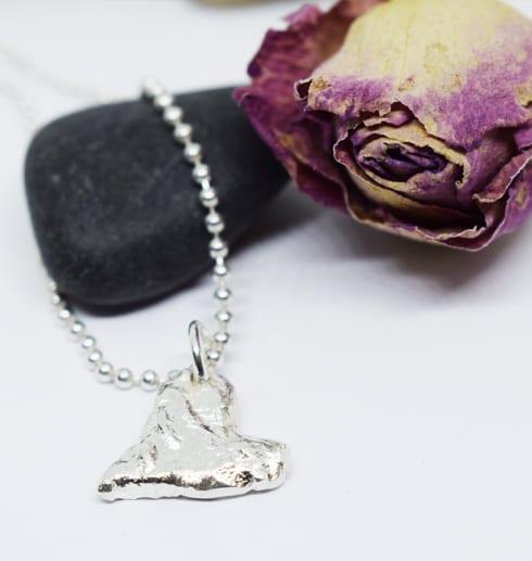 silverhjärta i kedja på svart sten med ros