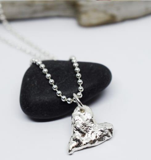 massivt silverhjärta på svart sten med träbit bakom