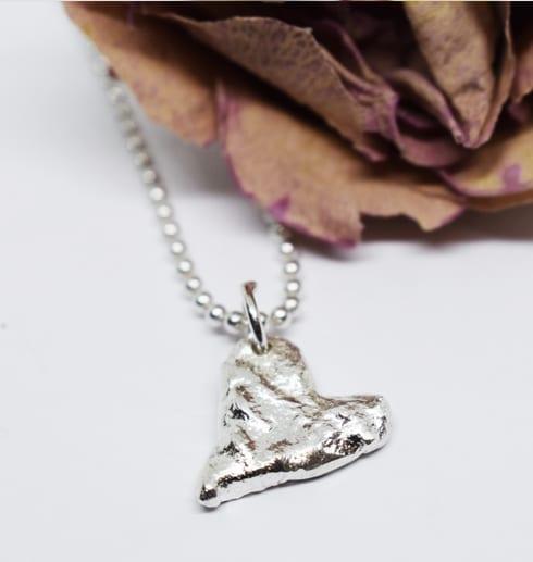 massivt silverhjärta på vit botten med ros