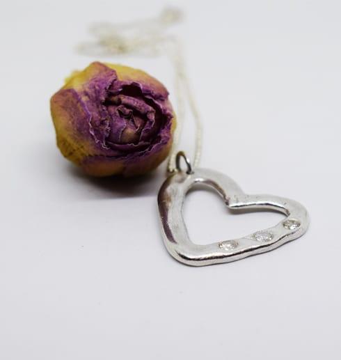 silverhalsband i form av ett hjärta med stenar på vit bakgrund med rosa ros