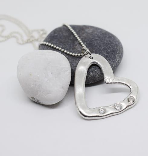 silverhalsband i form av ett hjärta med stenar på stenar