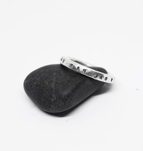 silverring med text på sten med vit bakgrund