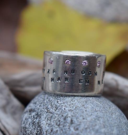 bred silverring med text och stenar på stenar utomhus