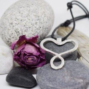 silversmycke i läderrem på stenar med lila ros