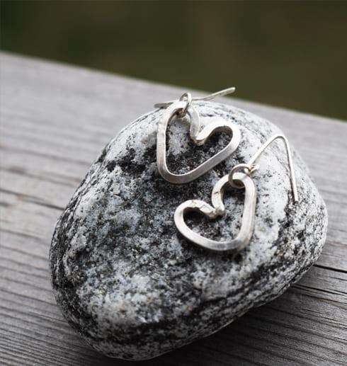 örhängen i form av hjärtan på grå sten utomhus