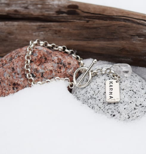 silverarmband på stenar med trädgren och snö utomhus