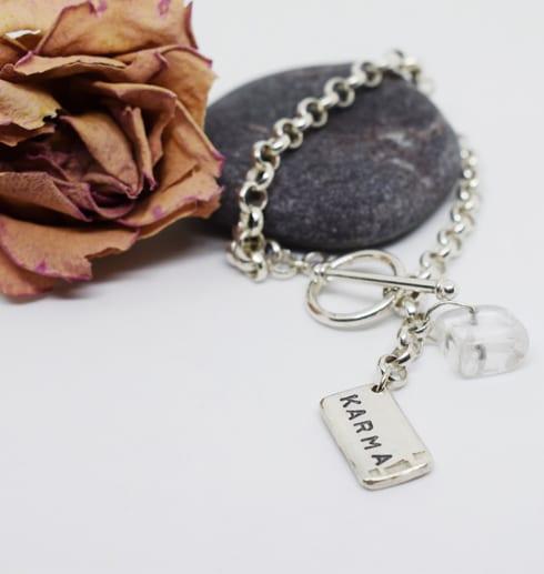 silverarmband med bricka på vit botten med ros och sten