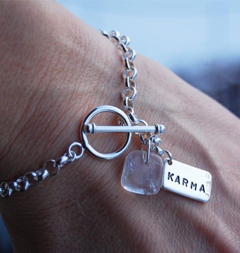 silverarmband med bricka med texten KARMA på handled