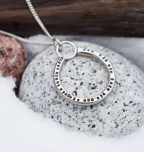 silverhalsband med lång text på stenar med snö utomhus