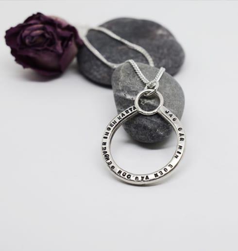 silverhalsband med tetx på stenar med ros bakom