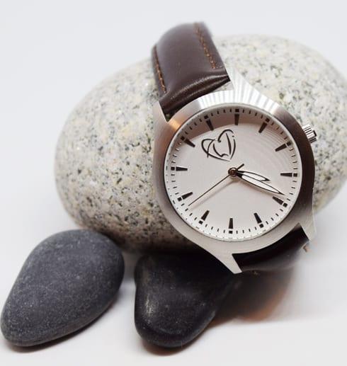 klocka med brunt läderarmband på stenar