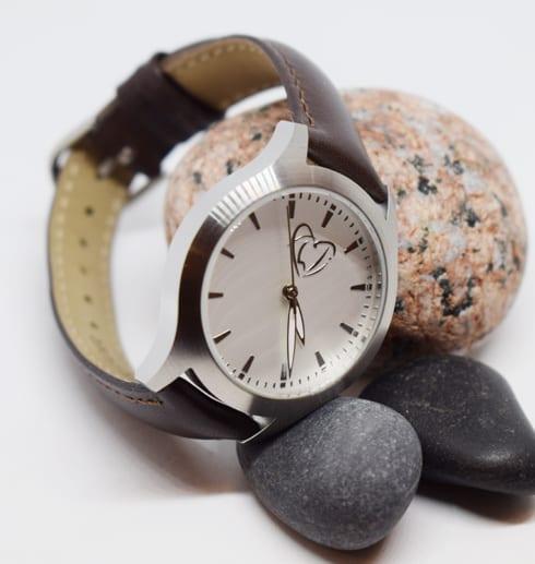 klocka med brunt läderarmband med stenar i bakgrunden