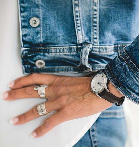 klocka med brunt läderarmband på handled på kvinna med jeanskläder
