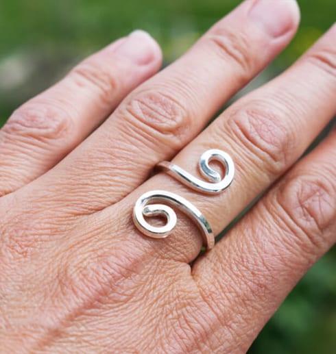 silverring med krumelur på finger utomhus