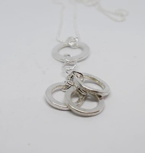 silverhalsband med ringar på vit botten