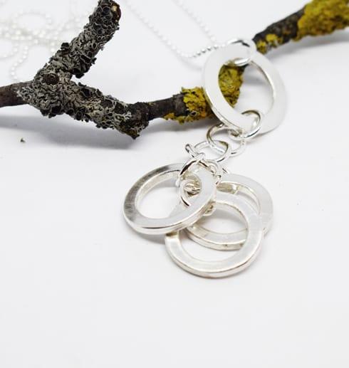 silverhalsband med ringar på vit botten med trägren