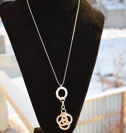 halsband i silver hängande på svart byst utomhus