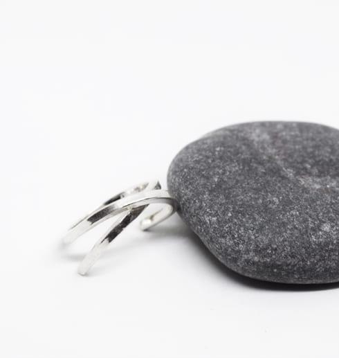 silverring på vit bakgrund med grå sten bredvid