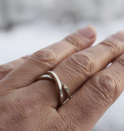 silverring i form av en kryssring på finger utomhus