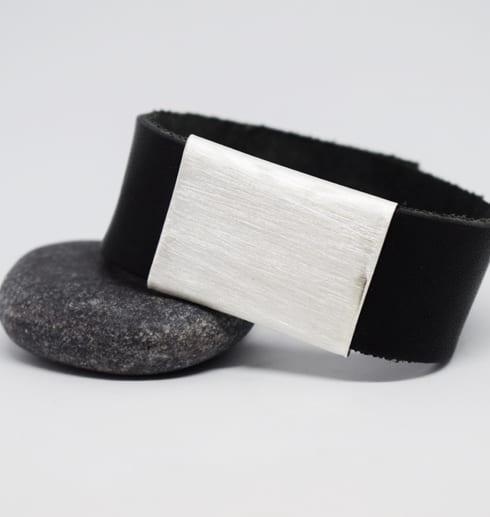 läderarmband med silverbricka på grå sten med vit bakgrund