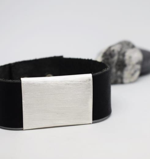 läderarmband med silverbricka på vit botten med sten i bakgrunden