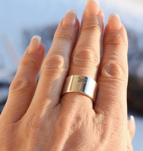 bred silverring med lekryss på finger utomhus