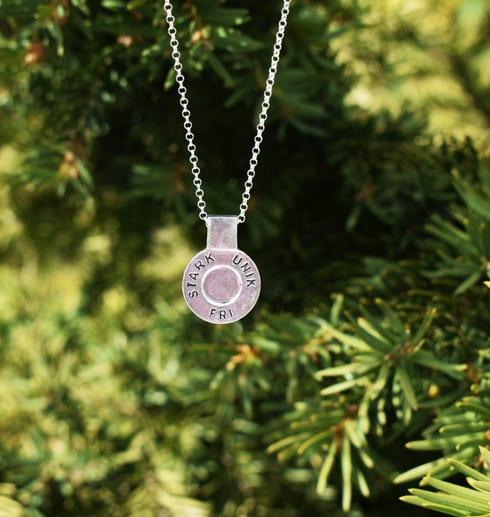 runt silversmycke i kedja med texten STARK, UNIK, FRI hängande i luften utomhus framför enbuske