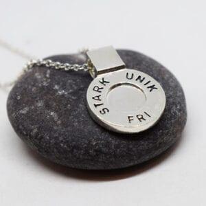 runt silversmycke i kedja med texten STARK, UNIK, FRI påmörkgrå sten