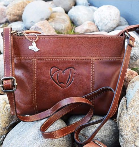 brun skinnväska med silversmycke mot stenar