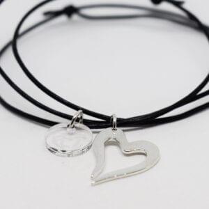 silverhjärta i läderrem på vit bakgrund