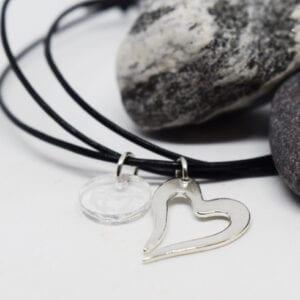 litet silverhjärta i läderrem på vit bakgrund med sten bakom