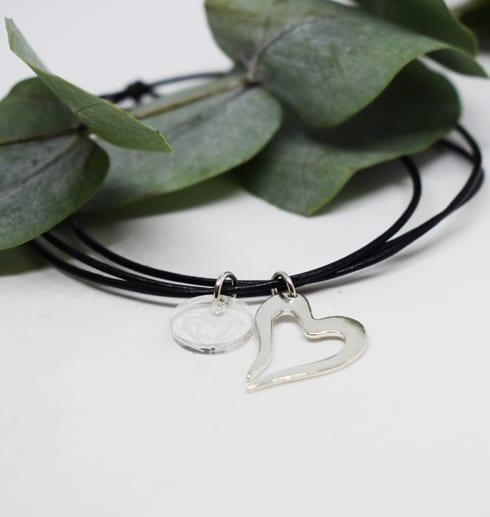 litet silverhjärta i läderrem på vit bakgrund med grön kvistbakom