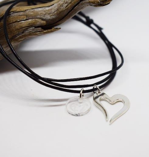 litet silverhjärta i läderrem på vit bakgrund med trädgren bakom