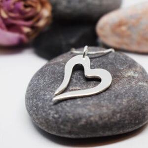 silverhjärta i kedja på grå sten med stenar och ros bakom