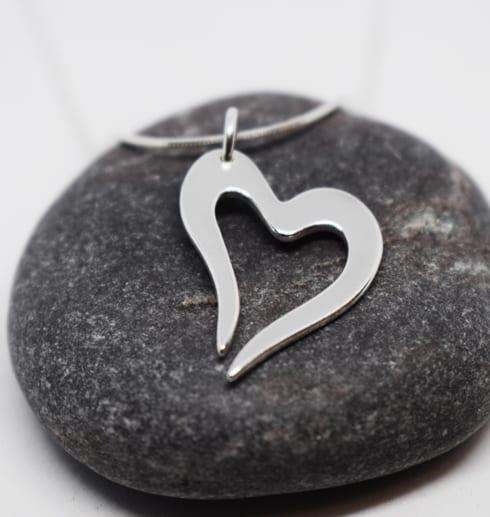 silverhjärta i kedja på grå sten