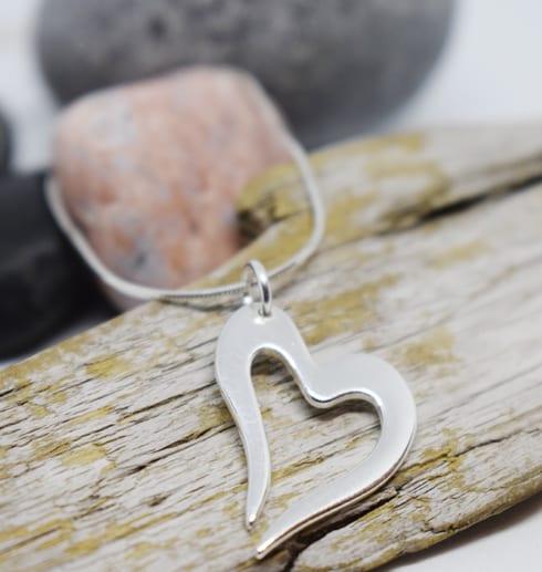 silverhjärta i kedja på träbit med stenar bakom