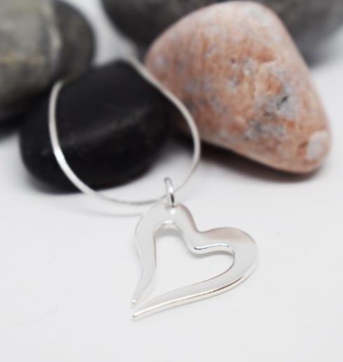 silverhjärta i kedja på vit bakgrund med stenar bakom