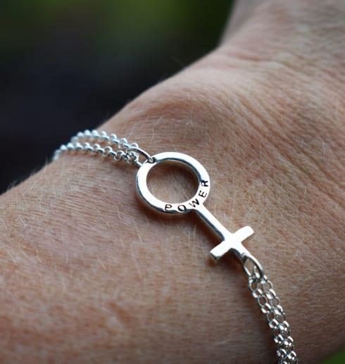 kvinnosymbolen som armband på en arm- girlpower