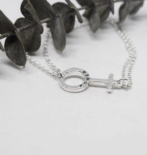 kvinnomärket som armband i silver mot vit bakrund med en grun kvist liggandes bredvid