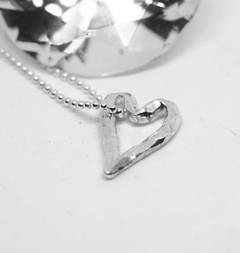 silverhjärta i kedja på vit bakgrund med kedja